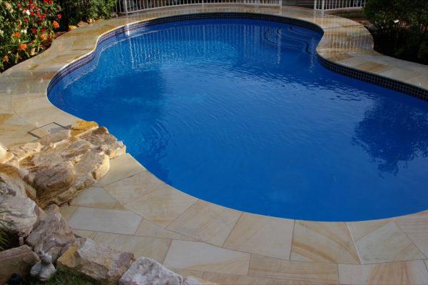 Teakwood sandstone pool paving and matching pool coping